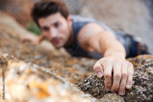 Fotografiet  Man reaching for a grip while he rock climbs