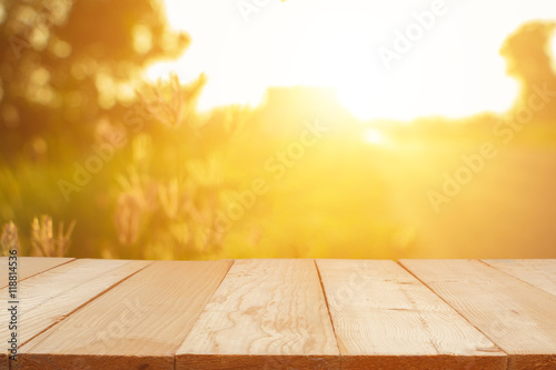 Obraz Empty wooden table with autumn for a catering or food background with a country outdoor theme,Template mock up for display of product,Blurred grass in bright morning. - fototapety do salonu