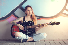 Girl Sitting Near A Graffiti Wall And Plays Electric Guitar.