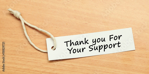 white tag on wooden background with word quotes of thank you for your support