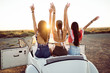 Three pretty young women driving on road trip on beautiful summe