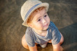 A cute little boy with summer hat playing in the sand on the bea
