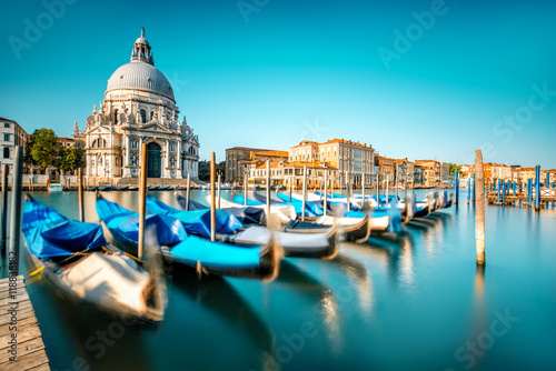 Foto auf AluDibond Venedig Venice cityscape view on Santa Maria della Salute basilica with gondolas on the Grand canal in Venice. Long exposure image technic with motion brured boats
