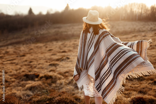 Photo  happy boho woman, walking towards sun, wearing hat and poncho at