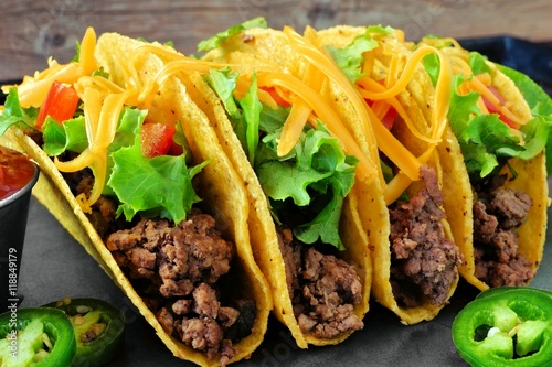 Group of hard shelled tacos with ground beef, lettuce, tomatoes and cheese close up
