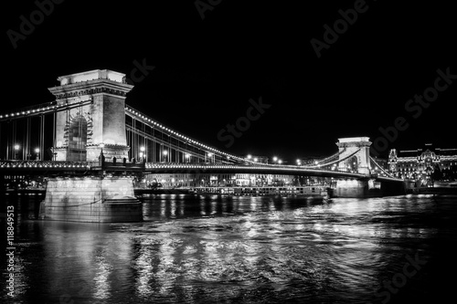 Fotobehang Boedapest A black and white perspective on the historic Chain Bridge in Budapest at night reflecting in the Danube River.