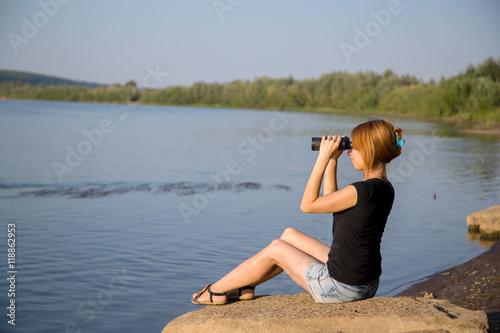 Fotobehang Ontspanning girl near water sits on a rock and looking through binoculars