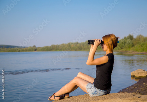 Fotobehang Ontspanning young girl sitting on a stone near the river and looks through binoculars