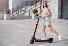 Joyful Woman Riding A Kick Scooter