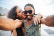 Smiling man and woman making selfie photo on smartphone