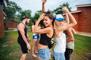 Young cheerful happy teens dancing at the picnic area