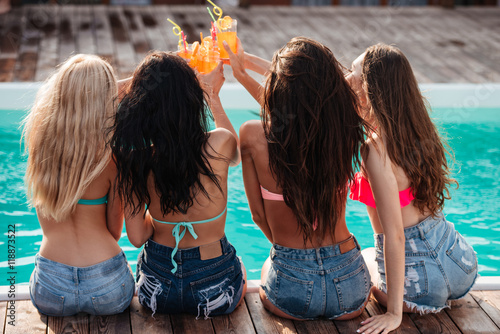 Valokuva  Attractive women celebrating and toasting at party near swimming pool