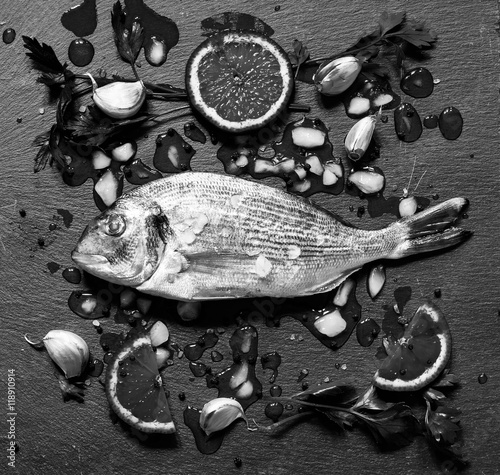 Photo  Fresh Fish Orata Over a Black stone with vegetables