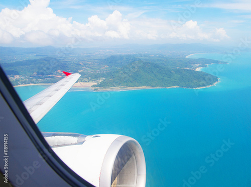 Photo  Airplane fly above sea island - Travel Concept