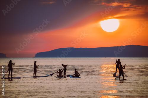 Plakat SUP w zachodzie słońca / grupa SUP`s na słońcu
