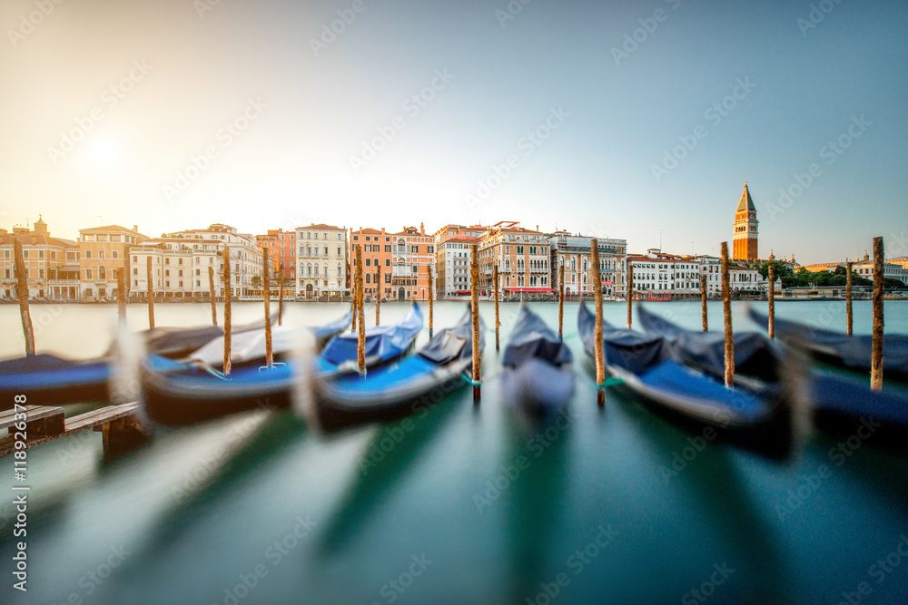 Fototapety, obrazy: Venice cityscape view on Grand canal with colorful buildings, gondolas and San Marco campanille at the sunset. Long exposure image technic with motion blurred boats and glossy water
