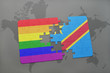 puzzle with the national flag of democratic republic of the congo and gay rainbow flag on a world map background.