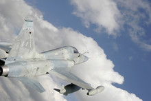 Fighter Jet Against White Clouds And Blue Sky