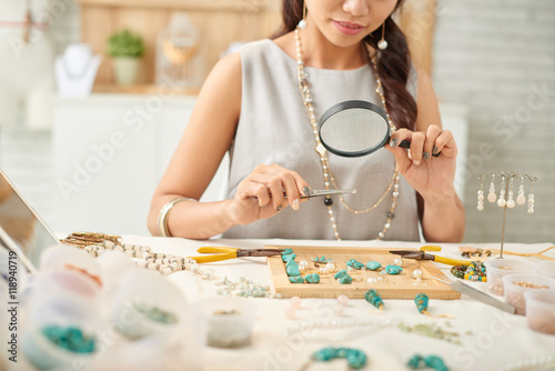 Jewelry designer looking at her work with magnifying glass Canvas Print