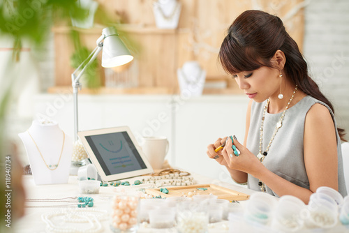 Pretty Vietnamese woman working with gemstones in her studio Canvas Print