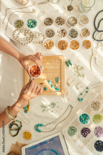 Jewelry designer choosing gems for new work, view from the top Wallpaper Mural