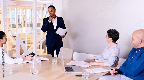 Fotografie, Obraz  Businessman standing in front of 3 colleagues in board room busy giving a presentation about their company possibly entering into a collaboration with someone else