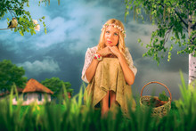 A Charming Young Woman With Long Blond Hair And A Cirlet Of Flowers Is Sitting On The Grass. The Background Is Blue And Grey Sky. There Is A Bird On The Branch On The Left And A Birch On The Right