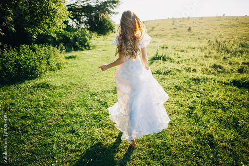 Fotografija  Young girl in a white dress in the meadow