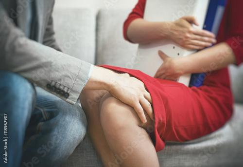 Fototapeta Sexual harassment at work. Man touching secretary's knee. obraz