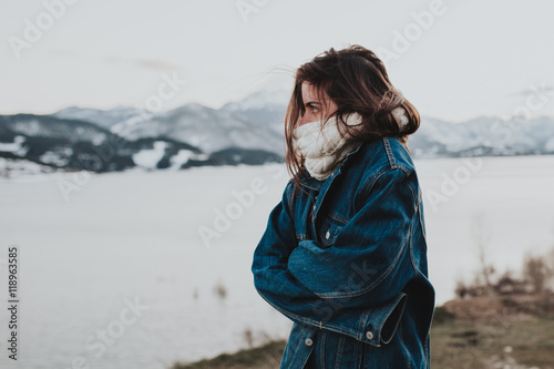 Young brunette woman cold at winter riverside
