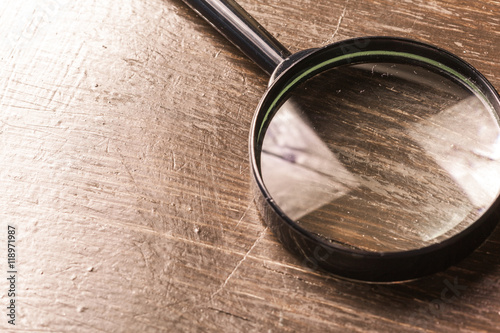 Fotografia  magnifying glass on the  wooden background