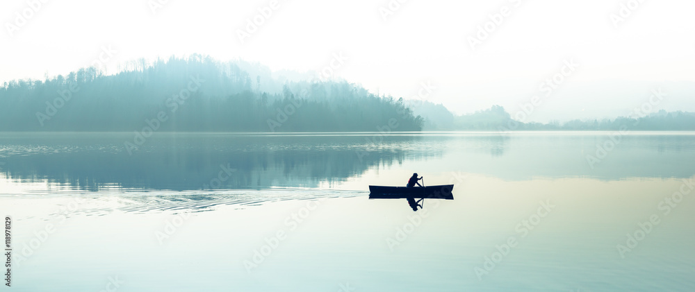 Fototapety, obrazy: Fog over the lake. Silhouette of mountains in the background. The man floats in a boat with a paddle.