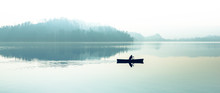 Fog Over The Lake. Silhouette Of Mountains In The Background. The Man Floats In A Boat With A Paddle.