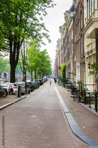 Photo  Narrow Cobbled Street lined with Trees and Brick Building alongside in Amsterdam