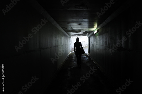 Fotografie, Tablou  Silhouette of a young woman walks alone in a dark tunnel