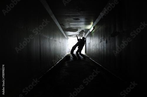 Man attacks a woman in a dark tunnel Fototapete