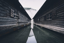 Two Wooden Cabins Reflected On...