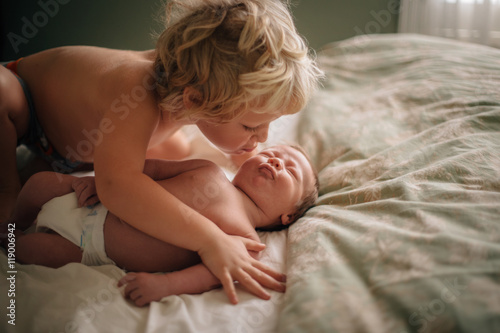 Big brother kissing baby on bed