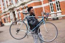 Young Man Carrying His Bike