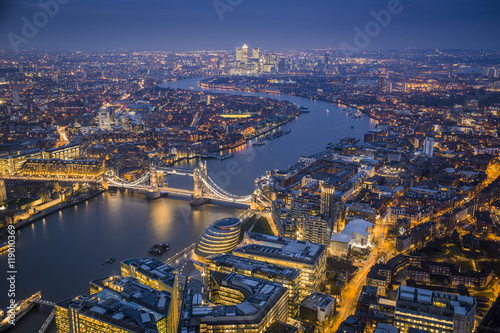 Poster London London, England - Aerial Skyline view of London with the iconic Tower Bridge, Tower of London and skyscrapers of Canary Wharf at dusk