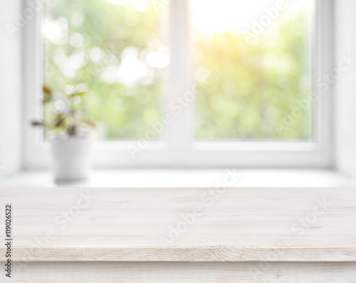 Wooden table on defocused summer window with flower pot background