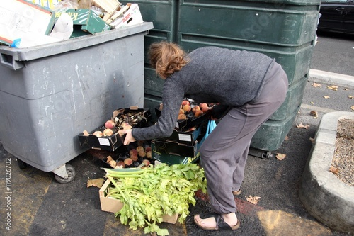 Fotografie, Obraz  Une jeune femme étudiante récupère des fruits et legumes jetés dans les poubelle