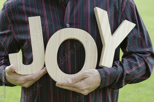 Fotografie, Tablou  Wooden letters of the word joy - close up of man's hands holding the word with a Holiday themed red plastic container