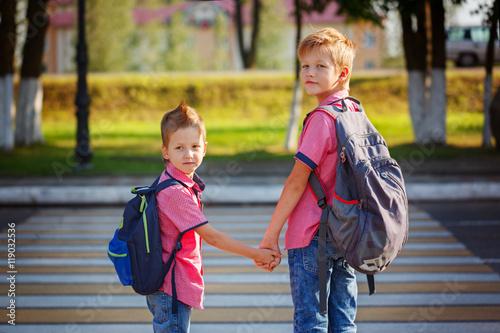 Zdjęcie XXL Portret dwa uroczej chłopiec z plecakiem blisko pieszy crossin