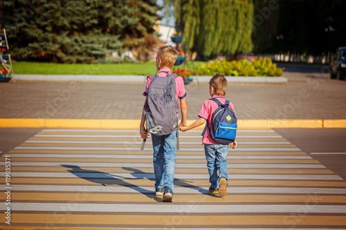 Plakat Dwóch chłopców z plecakiem spaceru, trzymając w ciepły dzień na drodze