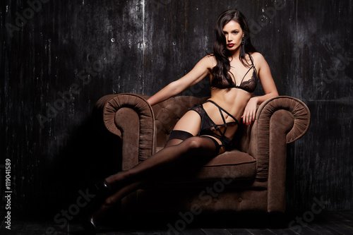 Fotografie, Obraz  Sexy fashion brunette woman with dark hair sitting on the velvet armchair in bla