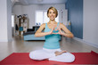 charming woman sitting on yoga mats and shows hand in heart form love. soft focus on hand
