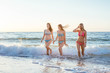 three girls having fun on beach, friends on beach in sunset light