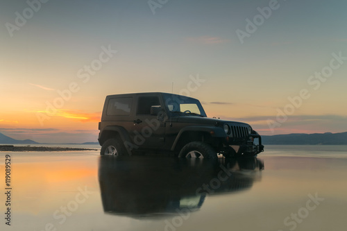 Fotomural Car 4x4 in the mud against a beautiful sunset.