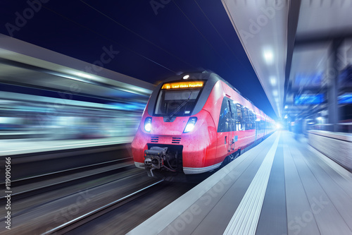 Foto  Modern high speed red passenger train at night